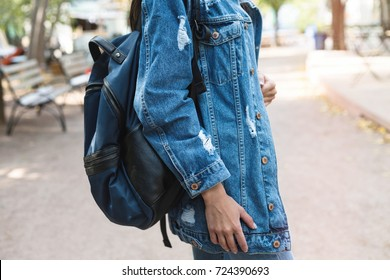 Fashionable young woman in jeans, long jeans jacket and handbag on the city streets. Fashion.Stylish.Close up image of fashion details, jeans jacket, stylish bag.
