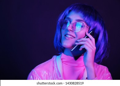 Fashionable young woman in neon light is holding a smartphone. The girl is wearing a wig, glasses and a shiny, halo jacket. Copy space.