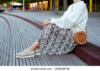 Fashionable young woman in platform beige shoes, white sweater, skirt with snake print and straw circle handbag in hand on the city street. Street style.