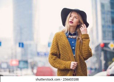fashionable young woman posing outside in a city street