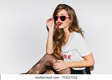 Fashionable young woman with red lips holding funny sunglasses on white background. Interested beautiful girl in pantyhose sitting during indoor photoshoot.