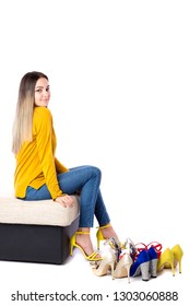 Fashionable young woman sitting on the sofa with many shoes on the floor on white background. Shopping concept