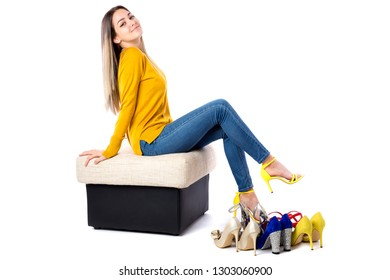 Fashionable young woman sitting on the sofa with many shoes on the floor over white background. Shopping concept