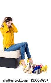 Fashionable young woman sitting on the sofa with many shoes on the floor against white. Shopping concept