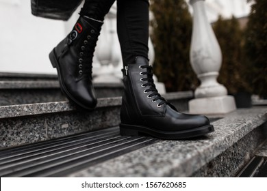 Fashionable young woman stands on the stone steps in the city in black trendy leather lace-up boots in vintage jeans. Close up of female legs in fashion autumn-spring shoes.New stylish shoe collection