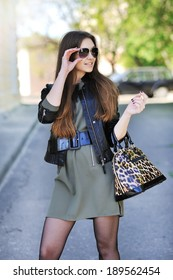 Fashionable young woman in stylish dress and sunglasses
