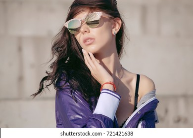 Fashionable young woman in sunglasses, lilac short windbreaker and jeans. Sits on a concrete structure, bare shoulder. Women's fashion. Urban way of life.