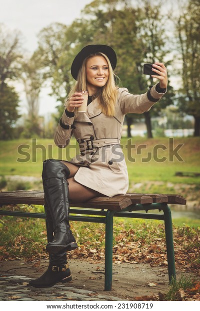 Fashionable young woman with takeaway coffee wearing coat, boots and hat sitting on the bench in park in autumn taking a selfie with smart phone.
