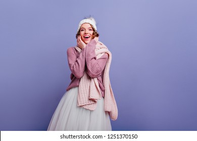 Fashionable young woman in trendy winter accessories posing in studio. Smiling lovable girl in sweater standing on purple background.