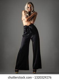 fashionable young woman in trousers posing on grey background