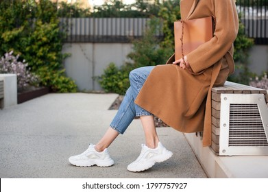 Fashionable young woman wearing beige wool coat and blue jeans. She is holding trendy tan tote bag in hands. Street style.