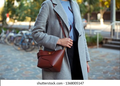 Fashionable young woman wearing grey coat, striped vest blouse, pants, holding brown bag . Street style.