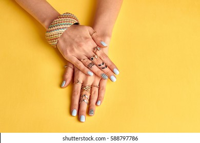 Fashionable youth bijouterie on female hands. Preparing to summer. Bijouterie and jewelry. Beautiful well-groomed female hands with nail polish.