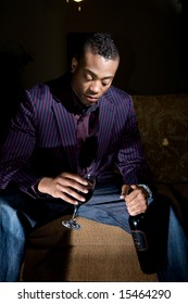 a fashionable, youthful african american contemplates drinking more wine