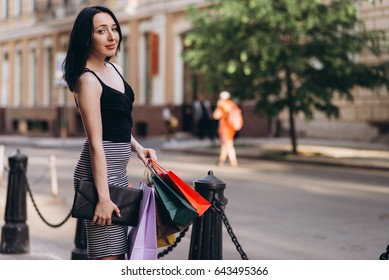 Fashionably dressed woman with colored shopping bags on the streets, shopping concept