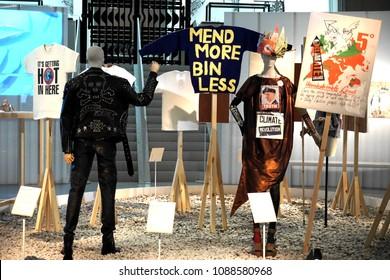 Fashioned from Nature at V&A London, UK - May 3rd 2018: Katherine Hamnett 'Clean up or die' jacket 1989, Bridget Harvey 'Mend more' jumper 2015, Vivian Westwood dress 2012