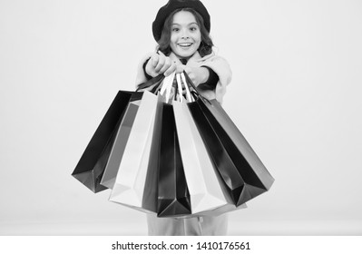 Fashionista adore shopping. Obsessed with shopping. Girl cute kid hold shopping bags on yellow background. Mid season sale. Shop with discount card. Get discount shopping on birthday or holiday.