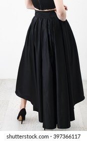 Fashionista in black shirt and long skirt on white background