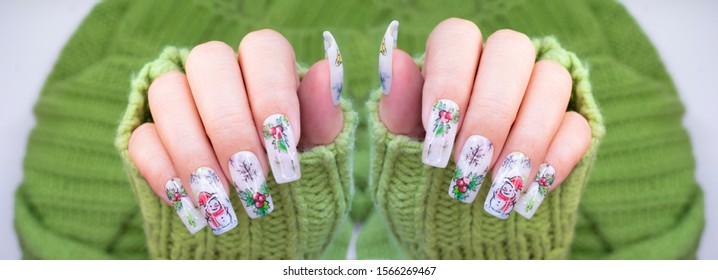 Fashionista woman wear light green knitting sweater with beautiful long acrylic fingernail square shape painting cute snowman snowfleke holly fruit red berry and golden bell christmas gel nail design