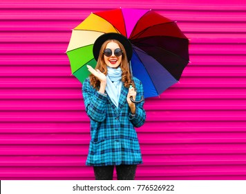 Fashionl smiling woman holds colorful umbrella wearing black hat checkered coat jacket over red background