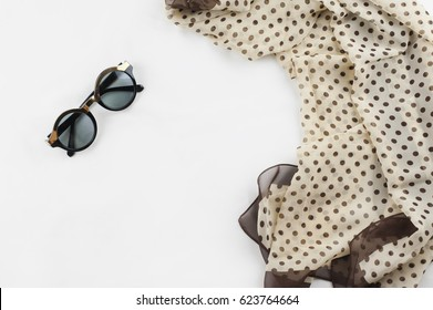 Fashion.Summer girl clothes set, accessories. Creative look, on the white background. Brown scarf dot pattern, sunglasses. Fashion set outfit. Unusual fashion essentials.Top view