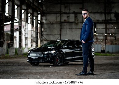 Fasion photoshooting of a man in elegant formal clothes. Young succesfull rich guy on black car background. Closeup.