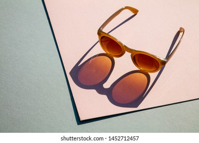 Fasionable summer sunglasses with long shadow on pink and blue background