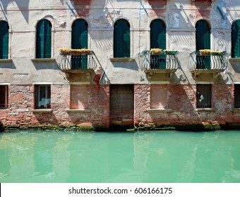 Fassade of old venetian rustic house standing in water. Venice, Italy.