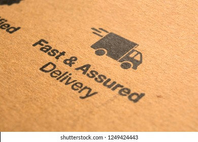 Fast and assured delivery concept printed on cardboard.