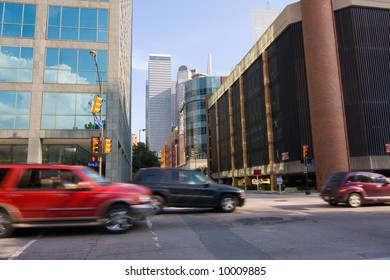 Fast automobile traffic moving through downtown city streets. Lots of motion blur.