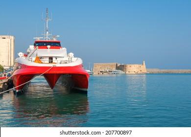 Fast catamaran ferry moored  in port of Heraklion. Venetian Fortress of Rocca al Mare in the background. Crete, Greece, Europe