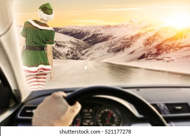Fast driver in car interior on winter road and green elf. Photo with mountains background and golden hour time sunset.