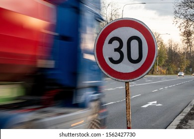 A fast driving blue speeding truck with motion blur effect near the traffic sign limiting the maximum speed to 30 kph or mph