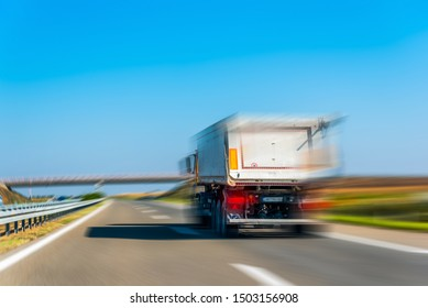 Fast driving lorry  in countryside landscape in sunny day. Highway view with blue sky.Truck with container.Cargo transportation concept. Blur effect.