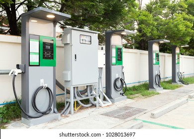 fast electric vehicle car charger with cable supply plugged and power supply box at EV station sites. EV car charging station in car park at supermarket ready to serve future automotive and city life.