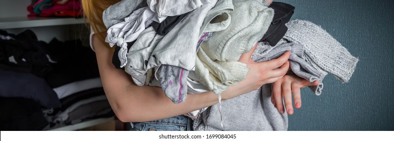 Fast fashion, the girl puts things in order in the closet. A bunch of colorful clothes. The concept of processing, second hand, eco, minimalism, consumption of goods.