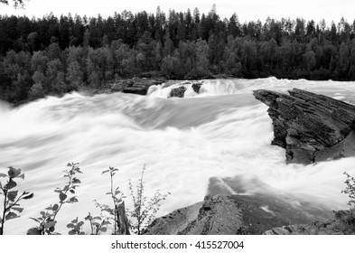 fast flowing flooded river current with violent waterfall