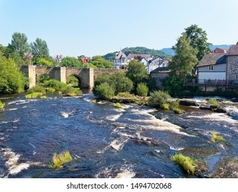 The fast flowing River Dee passes between wooded banks to the quaint old Welsh town of Llangollen on a hazy summer afternoon