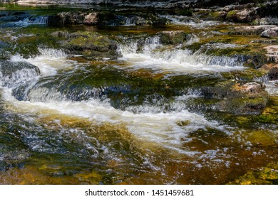 Fast flowing water of the River Ribble starts to blurr as it falls over rocks at Stainforth Force