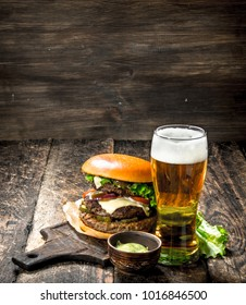 Fast food. A big burger with beef and a glass of beer. On a wooden background.