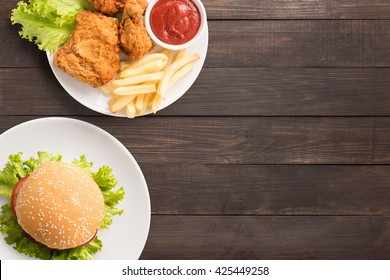 Fast food big hamburger on wooden background. Fast food set fried chicken and french fries. Take away fast food.