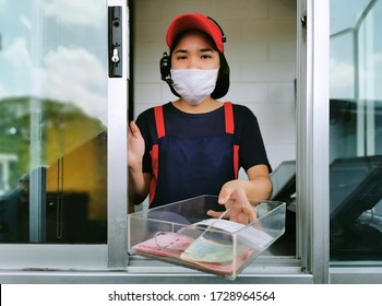 fast food cashier in drive thru service waring hygiene face mask to protect coronavirus pandemic or covid-19 virus outbreak is giving money change to customer.