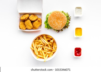 Fast food. Chiken nuggets, burgers and french fries on white background top view