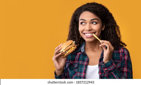 Fast Food. Closeup Portrait Of Smiling African American Woman Eating Burger And French Fries, Looking At Copy Space. Black Lady Holding And Biting Tasty Potato, Isolated Over Orange Background, Banner