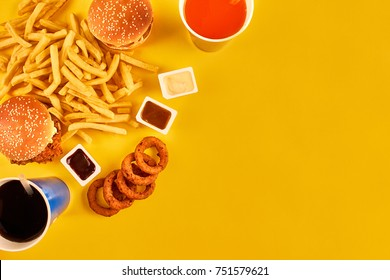 Fast food concept with greasy fried restaurant take out as onion rings, burger, fried chicken and french fries as a symbol of diet temptation resulting in unhealthy nutrition.