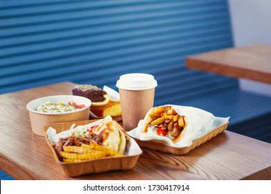 Fast food delivery.Take away menu in Greek restaurant.Traditional Mediterranean cuisine served on table in takeaway recyclable dishes.Fastfood order with empty space on paper coffee cup for cafe logo