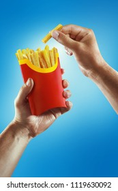Fast food and diet. Hands hold the French fries.