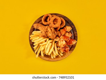 Fast food dish on yellow background. Fast food set fried chicken and french fries. Take away fast food.