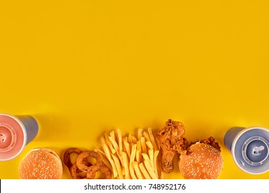 Fast food dish on yellow background. Fast food set fried chicken, meat burger and french fries. Take away fast food.