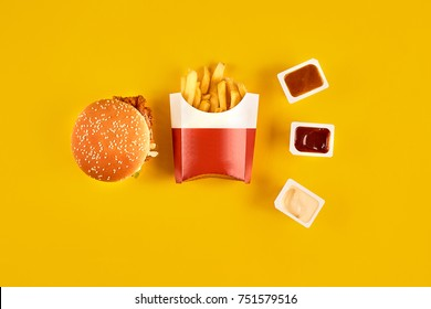 Fast food dish on yellow background. Fast food set meat burger, three sauce and french fries. Take away fast food.